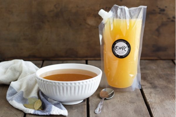Broth in a pouch sitting next to a bowl