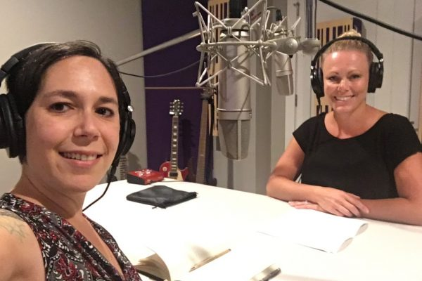 Stephanie in front of microphones with headphones on alongside her guest