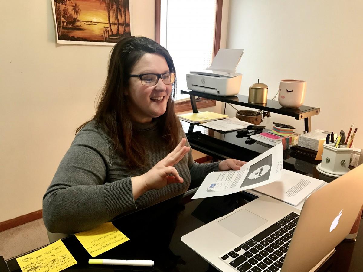 Britni Eisenmann smiling in front of her laptop.