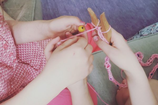Two children doing crafts with beads and yarn