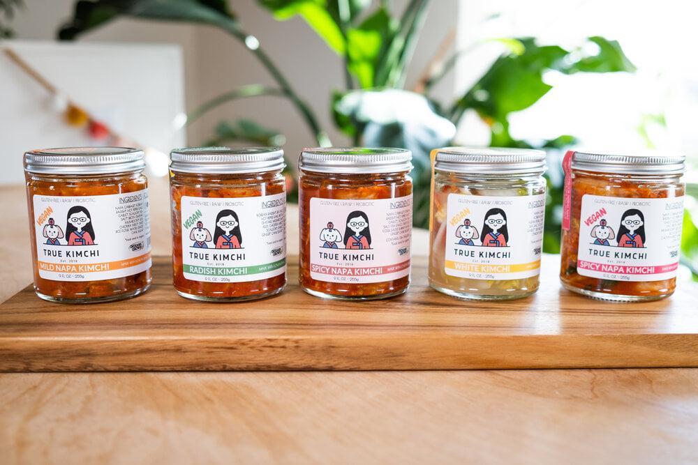 5 jars of True Kimchi flavors on a shelf: Mild Napa, Radish, Spicy Napa, White, and Vegan Spicy Napa