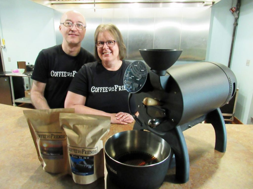 Aaron and Michele Cantrell with two bags of coffee beans and their coffee roaster