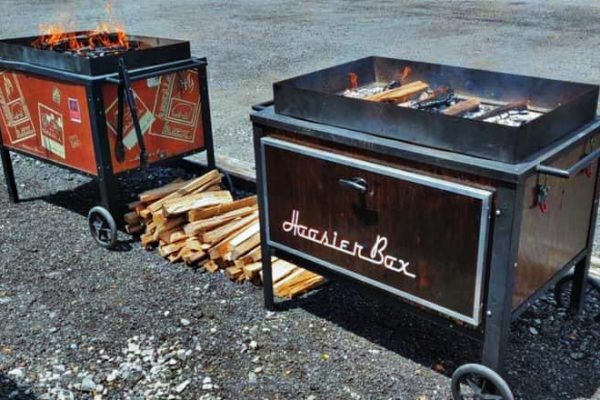 Two smoking roaster boxes in a parking lot.
