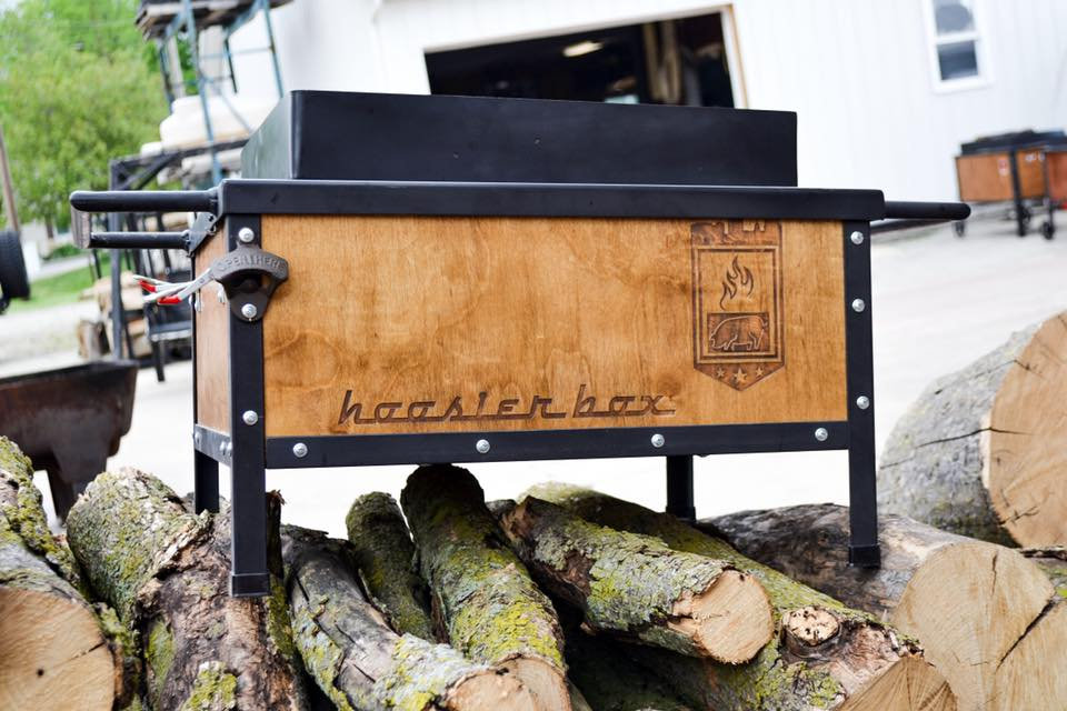 Wooden roaster box balanced on a pile of logs.