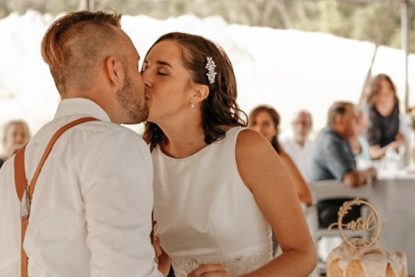 A video still of a bride and groom kissing