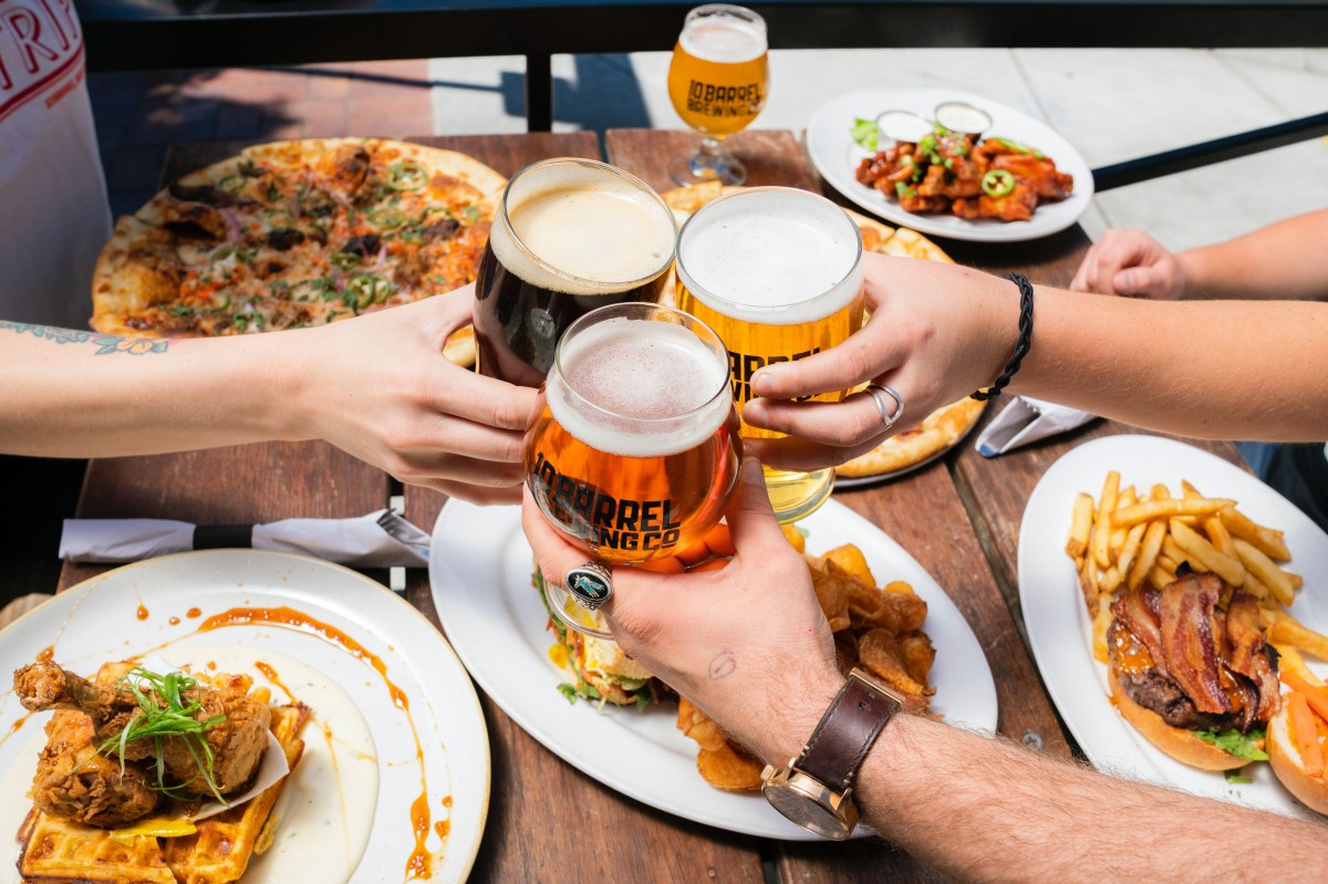 People clinking beer glasses with burgers in the background