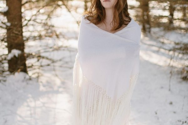 Bride wrapped in a knit shawl in the snow